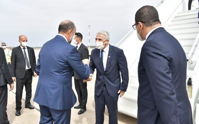 Morocco's Deputy Foreign Minister Mohcine Jazouli greets Foreign Minister Yair Lapid (center) at Rabat-Sale International Airport, August 11, 2021 (Shlomi Amsalem, GPO)