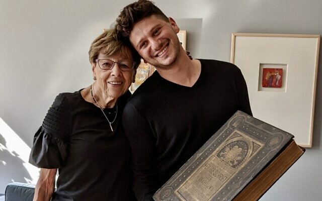 Susi Kasper Leiter and Jacob Leiter hold family bible, August 12, 2021. (Jacob Leiter/Courtesy)