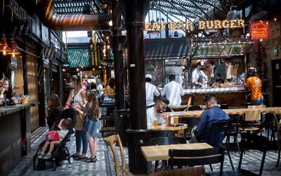 Customers at restaurants at the Sarona market in Tel Aviv on April 21, 2021. (Miriam Alster/Flash90)