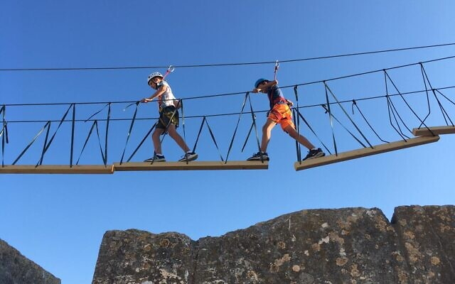 Walking across a hanging bridge in the Tower of David Museum ropes course, August 2021 (Jessica Steinberg/Times of Israel)
