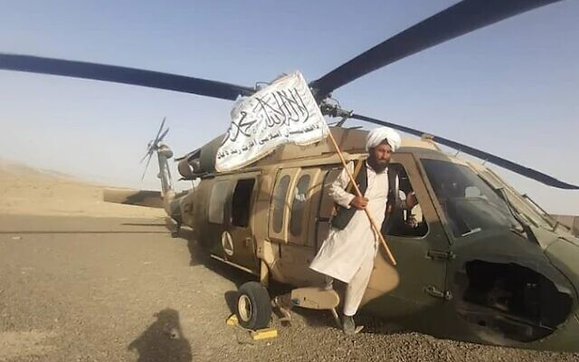 A Taliban member poses atop a US US-60 Black Hawk helicopter in Afghanistan, August 2021. (Uncredited)