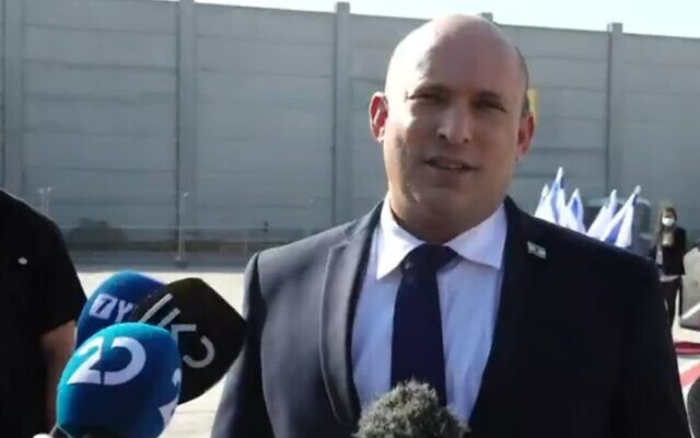 Prime Minister Naftali Bennett speaks to reporters at Ben Gurion Airport before flying to Washington, on August 24, 2021 (Channel 12 screenshot)