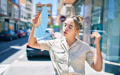 A young woman walks down the street hot weather (AaronAmat; iStock by Getty Images)