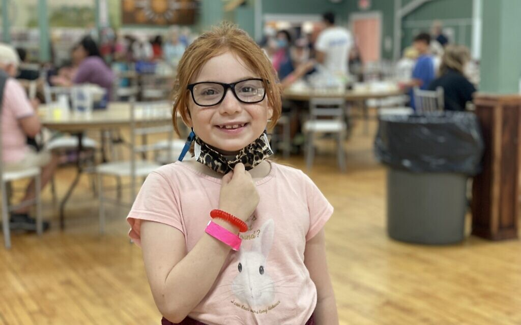 8-year-old Dinah Slepovitch has greeted Yiddishland attendees each morning for the last five years, and continues to do so in August 2021. (Danielle Ziri)