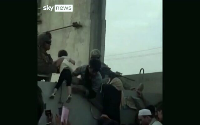 A soldier at Kabul Airport lifts a young child in a Sky News report from Afghanistan, August 19, 2021 (Screenshot)