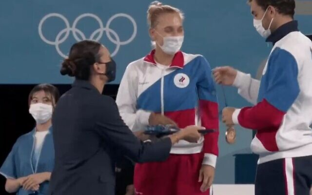 Russia's Aslan Karatsev attempts to give a gold medal to his mixed doubles tennis partner Russia's Elena Vesnina during the Tokyo 2020 Olympic medal ceremony at the Ariake Tennis Park on August 1, 2021. They actually won the silver medals (Twitter screenshot)