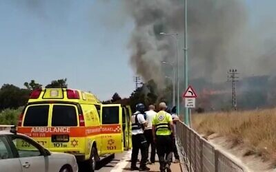 Paramedics look on as smoke rises from the scene where rocket landed near the northern city of Kiryat Shmona, on August 4, 2021. (Magen David Adom)