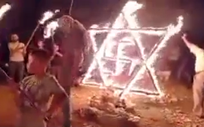 Palestinians set fire to a structure in the shape of a Star of David and a swastika near the town of Beita in the West Bank, on August 14. 2021. (Video screenshot)