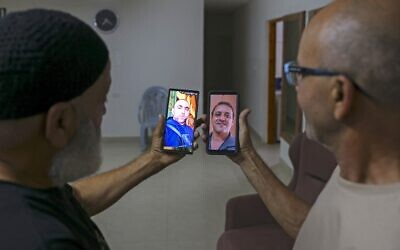 Malek Hassuna (L) carries a picture of his late son Mussa, who was shot dead on May 10, and Effi Yehoshua (R) carries a picture of his late brother Yigal, who was killed when a rain of stones hit his car on May 11, as they pose for a picture in Lod on August 18, 2021. (AHMAD GHARABLI / AFP)