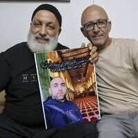 Malek Hassuna (L) carries a picture of his late son Mussa, who was shot dead on May 10, as he sits with Effi Yehoshua, brother of Yigal Yehoshua, killed on May 11, in Lod on August 18, 2021. (Ahmad Gharabli/AFP)