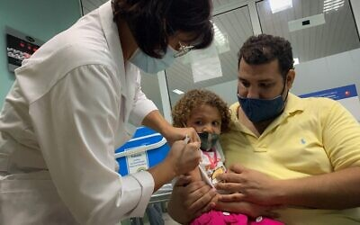 Pedro Montano holds his daughter Roxana Montano, 3, while she is being vaccinated against COVID-19 with Cuban vaccine Soberana Plus, on August 24, 2021 at Juan Manuel Marquez hospital in Havana, as part of a vaccine study in children and adolescents. (ADALBERTO ROQUE / AFP)