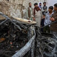 Afghan residents and family members of the victims gather next to a damaged vehicle inside a house, day after a US drone airstrike in Kabul on August 30, 2021. (WAKIL KOHSAR / AFP)