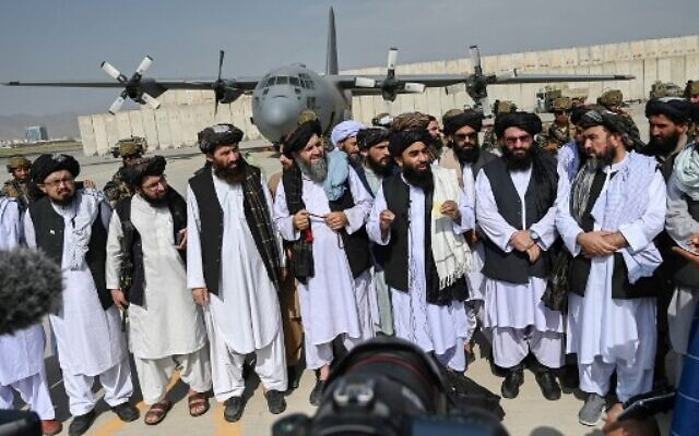 Taliban spokesman Zabihullah Mujahid (C, with shawl) speaks to the media at the airport in Kabul on August 31, 2021.  (WAKIL KOHSAR / AFP)