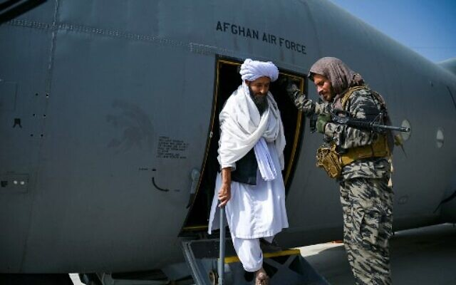 A member of the Taliban (center) walks out of an Afghan Air Force aircraft at the airport in Kabul, on August 31, 2021, after the US has pulled all its troops out of the country (Wakil Kohsar/AFP)