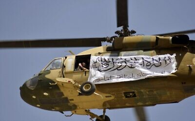 A helicopter displaying a Taliban flag fly above of supporters gathered to celebrate the US withdrawal of all its troops out of Afghanistan, in Kandahar on September 1, 2021. (JAVED TANVEER / AFP)