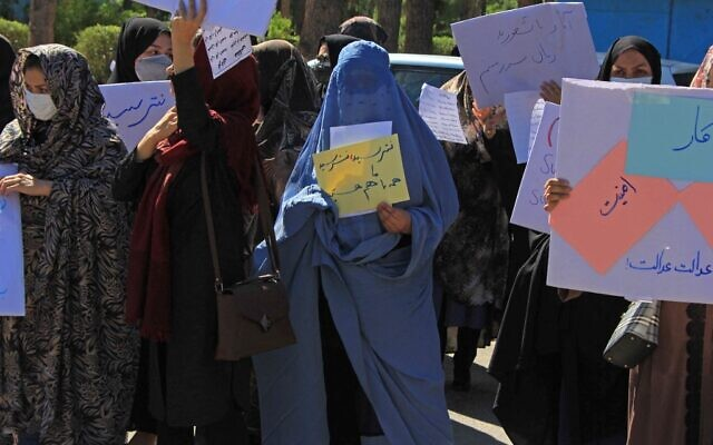 Afghan women hold placards and don burkas as they take part in a protest in Herat on September 2, 2021. (AFP)