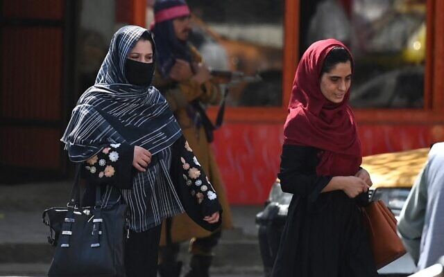 Afghan women walk past a Taliban fighter along a street in Kabul on September 2, 2021. (Aamir QURESHI / AFP)