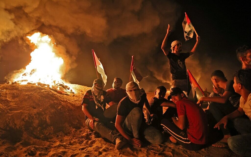 Palestinians gather on September 2, 2021 during a nighttime protest along the border fence with Israel, east of Khan Younis in the southern Gaza Strip (SAID KHATIB / AFP)