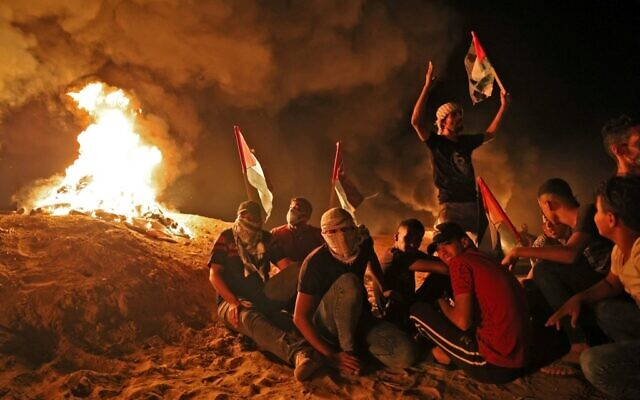 Palestinians gather, on September 2, 2021, during a nighttime protest along the border fence with Israel, east of Khan Younis in the southern Gaza Strip (Said Khatib/AFP)