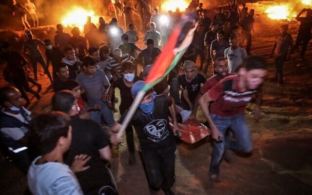Palestinians carry an injured protester during a night protest along the border fence with Israel, east of Khan Yunis in the southern Gaza Strip, on September 2, 2021. (SAID KHATIB / AFP)