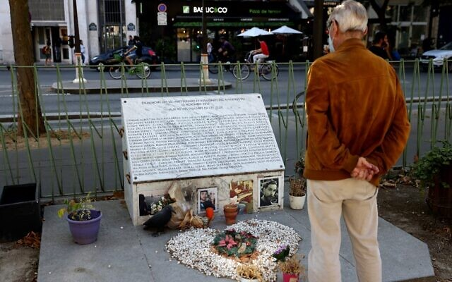 A man looks at the memorial plaque for a November 2015 terror attack near the Bataclan theatre and Cafe in Paris on September 3, 2021. (Thomas COEX / AFP)