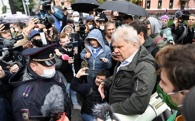 """Deputy of the Moscow City Duma Sergei Mitrokhin (R) speaks with a police officer, during a demonstration called to protest against the creation of the status of """"foreign agent"""" imposed to several independent and opposition media, in central Moscow, on September 4, 2021. (Natalia KOLESNIKOVA / AFP)"""