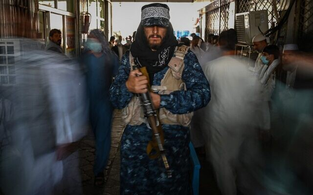 A Taliban fighter stands guard as people move past him at a market with currency exchange shops in Kabul on September 5, 2021. (Aamir Qureshi/AFP)