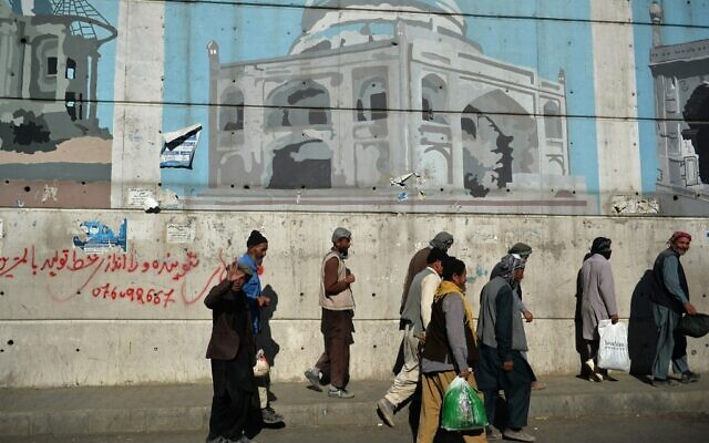 Afghan workers walk past a wall mural along a roadside in Kabul on September 5, 2021. (HOSHANG HASHIMI / AFP)