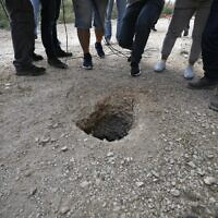 Police and journalists gather around a hole used by six Palestinians to escape from the Gilboa Prison, in northern Israel, on September 6, 2021. (Jalaa Marey/AFP)