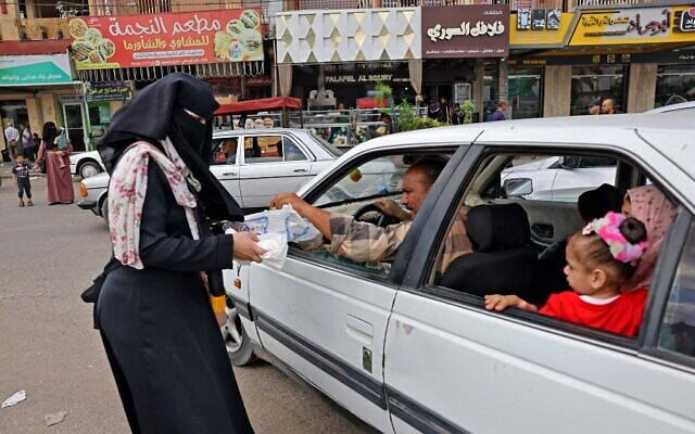 Supporters of the Islamic Jihad movement distribute sweets to celebrate the escape of six Palestinians from an Israeli prison, in Rafah in the southern Gaza Strip, on September 6, 2021. (Said Khatib/AFP)