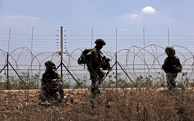 Israeli troops patrol along the security fence in the village of Muqeibila, near the northern West Bank city of Jenin, on September 6, 2021, following the escape of six Palestinian security prisoners from an Israeli prison. (Jalaa Marey/AFP)