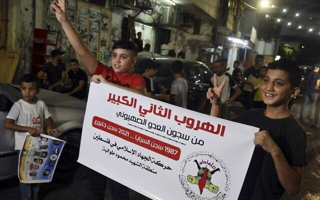 """Palestinians carry a poster of the Islamic Jihad terror group, reading in Arabic: """"The second great escape from the prisons of the Zionist enemy – 1987 Saraya Prison – 2021 Gilboa Prison,"""" following the escape of six Palestinians from an Israeli prison, in the Jenin refugee camp in the northern West Bank, on September 6, 2021. (JAAFAR ASHTIYEH / AFP)"""