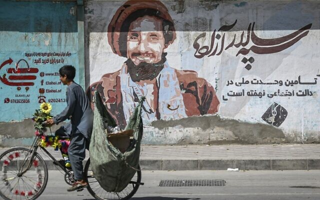 A boy peddles past a wall painting with a portrait of late Afghan commander Ahmad Shah Massoud in Kabul on September 8, 2021. (Aamir QURESHI / AFP)