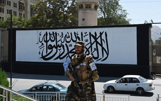 """A member of the Taliban Fateh, a """"special forces"""" unit, stands guard outside the US embassy in Afghanistan displaying a Taliban flag in the outer concrete wall in Kabul on September 8, 2021. (Aamir QURESHI / AFP)"""