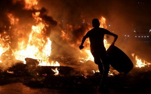 A Palestinian youth carries a tire before setting it ablaze, during confrontations with Israeli security forces following a rally in support of Palestinian prisoners held in Israeli jails, at the Hawara checkpoint near the West Bank town of Nablus, on September 8, 2021. (Photo by Jaafar ASHTIYEH / AFP)