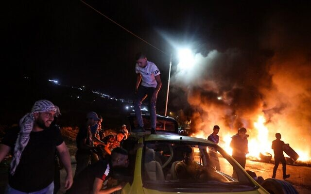 Palestinian demonstrators burn tires during confrontations with Israeli security forces following a rally in support of Palestinian prisoners held in Israeli jails, at the Hawara checkpoint near the West Bank town of Nablus, on September 8, 2021. (Jaafar ASHTIYEH/AFP)