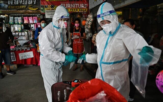 The research team from Chulalongkorn University's chemistry department collects sweat samples from vendors in a fresh market on September 8, 2021, as they develop a novel device that detects the COVID-19 coronavirus through specific odors, in Bangkok. (Lillian SUWANRUMPHA / AFP)