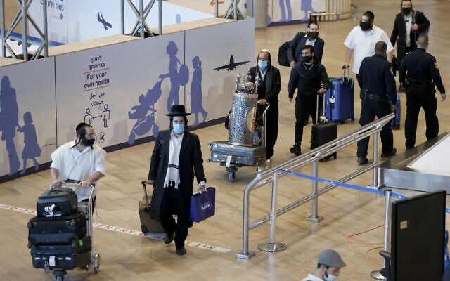 Illustrative — Ultra-Orthodox Jewish men carrying a scroll and luggage arrive at Ben Gurion airport on September 9, 2021, after spending the Rosh Hashanah (Jewish New Year) celebrations in the central Ukrainian town of Uman (JACK GUEZ / AFP)