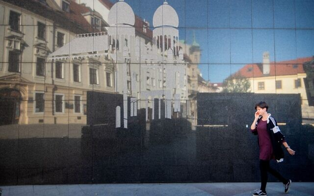 A woman passes a wall with an image of the former Neolog Synagogue next to the Holocaust Memorial located in the center of Bratislava's Old Town on September 9, 2021.(VLADIMIR SIMICEK / AFP)