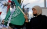 Arab-Israeli protesters lift spoons, reportedly the digging tool used by six Palestinian prisoners who escaped from Israel's Gilboa prison, as they demonstrate in the mostly Arab city of Umm al-Fahm in northern Israel, on September 10, 2021. (JACK GUEZ / AFP)