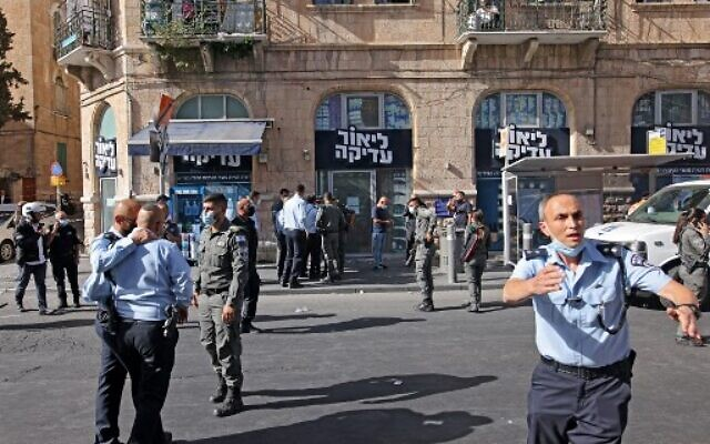 Israeli police officers gather outside the site of a stabbing attack, in Jerusalem on September 13, 2021. (AHMAD GHARABLI / AFP)