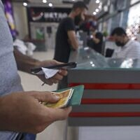 A Palestinian man receives financial aid at a supermarket in Gaza City, on September 15, 2021, as part of the UN's Humanitarian Cash Assistance program, supported by the state of Qatar. (Mahmud Hams/AFP)