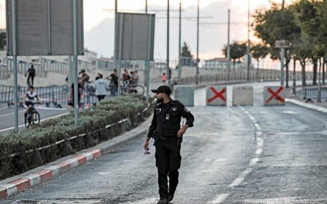 Illustrative: An Israeli policeman walks near cement cubes placed as a roadblock by Israeli security forces on a road linking the East Jerusalem Arab neighborhood of Beit Hanina with West Jerusalem on September 15, 2021 (Ahmad GHARABLI / AFP)