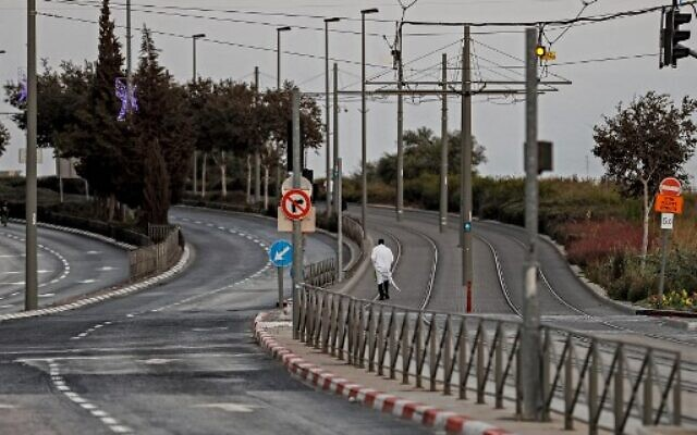A Jewish man walks along deserted light rails tracks linking the East Jerusalem Arab neighborhood of Beit Hanina with West Jerusalem on September 15, 2021, before the start of Yom Kippur (Photo by Ahmad GHARABLI / AFP)