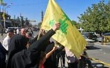 Lebanese people wave a Hezbollah flag as tankers carrying Iranian fuel arrive from Syria at al-Ain in east Lebanon's Bekaa Valley, on September 16, 2021. (AFP)