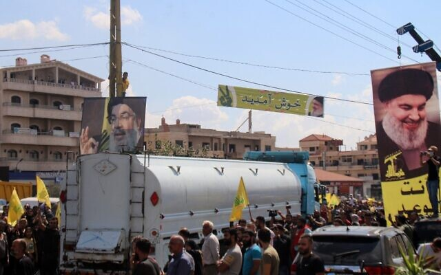 People hold portraits of the head of Hezbollah, Hassan Nasrallah, as they gather to welcome tankers carrying Iranian fuel, upon their arrival from Syria in the city of Baalbeck, in Lebanon's Bekaa valley, on September 16, 2021. (AFP)