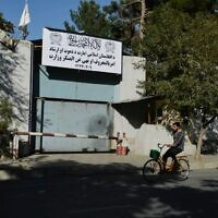 A man rides his bike past an entrance gate with a sign of the Ministry for the Promotion of Virtue and Prevention of Vice, which replaced the ministry of women's affairs, in Kabul on September 17, 2021 (Hoshang Hashimi / AFP)