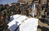 A Yemeni soldier takes a selfie as others surround body bags containing the corpses of newly executed men, convicted of involvement in the assassination of Houthi political leader Saleh al-Sammad three years ago, at a public square in the Yemeni capital Sanaa, on September 18, 2021. (Mohammed Huwais/AFP)