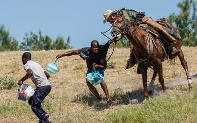 A United States Border Patrol agent on horseback tries to stop a Haitian migrant from entering an encampment on the banks of the Rio Grande near the Acuna Del Rio International Bridge in Del Rio, Texas, on September 19, 2021. (Paul Ratje/AFP)