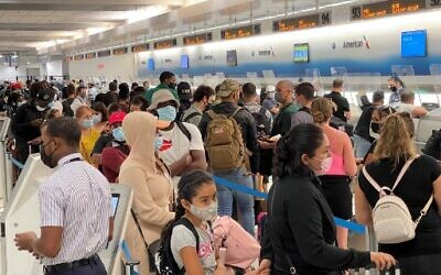 In this file photo travellers line up at Miami International Airport (MIA) on August 2, 2021.  (Photo by Daniel SLIM / AFP)